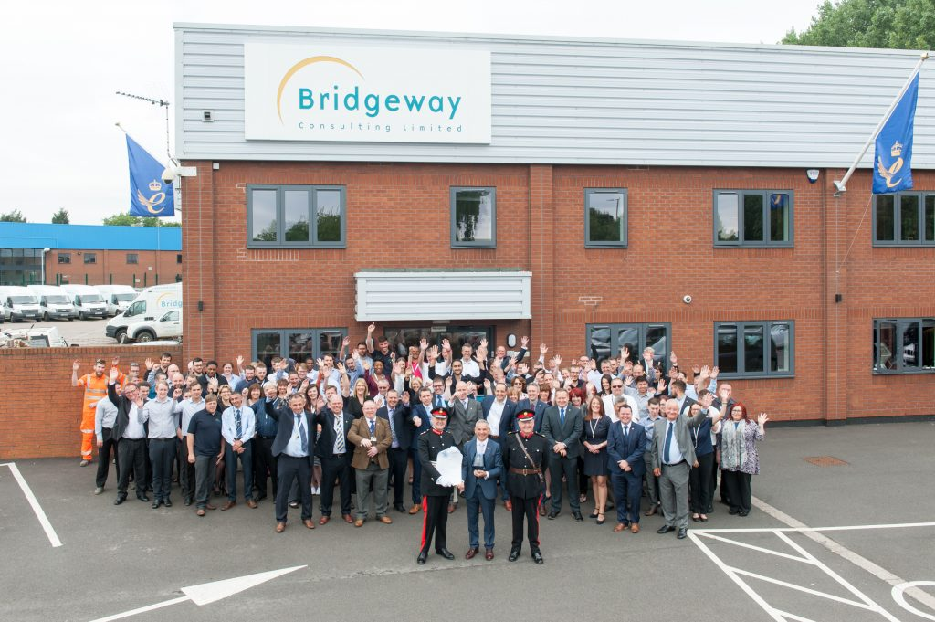 Bridgeway staff outside its Nottingham headquarters with the Queen's Award flags flying from the side of the building.